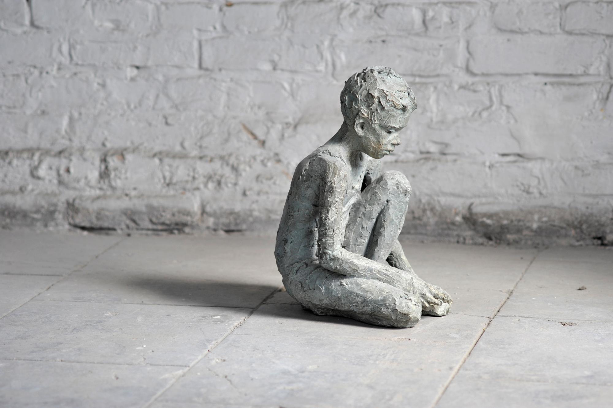 Jungendarstellung auf dem Boden hockend in Bronze gegossen
