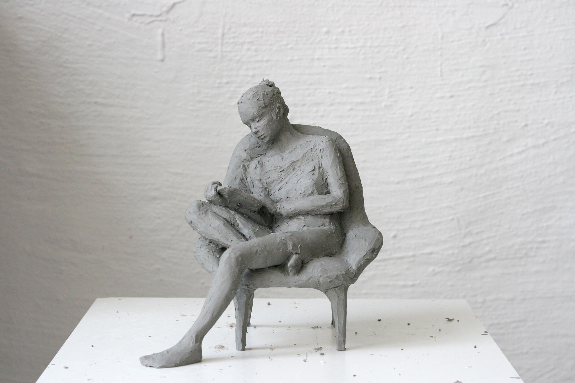 Eine junge Frau sitzt in einem Buch versunken auf einem Sessel.